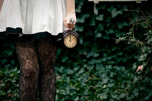 Kvinde står med gammelt ur