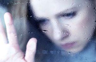 Kvinde ved vindue er trist på grund af råb og skrig