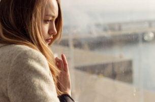 Kvinde ved vindue prøver at leve med det, der har såret hende