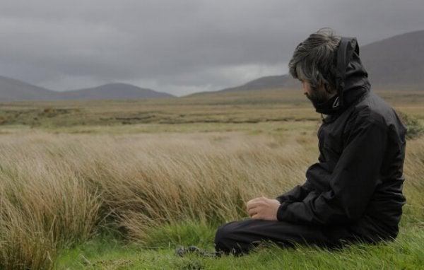 Mand på mark nyder stilhed alene