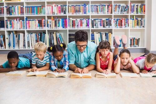 Børn læser bog på gulv med god lærer