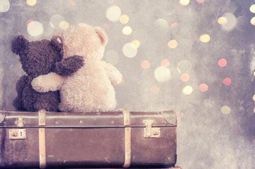 To bamser sidder på kuffert og krammer