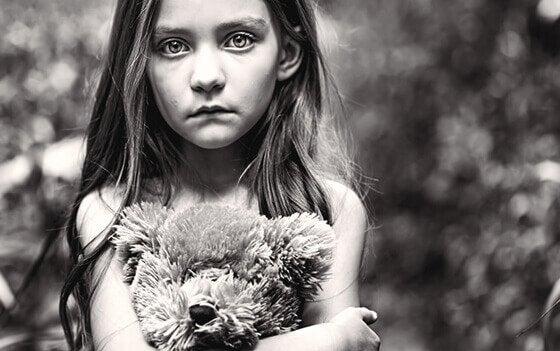 Pige mærket af giftige forældre krammer bamse