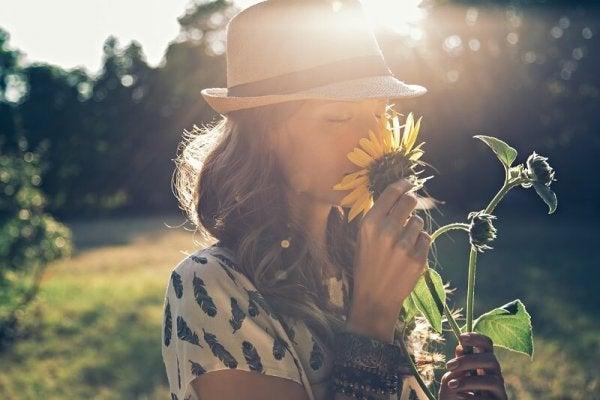 Kvinde dufter til blomst og anvender positiv tænkning