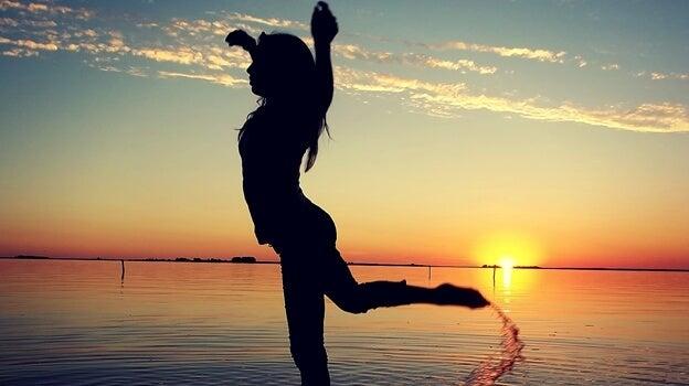 Kvinde nyder fordele ved dans foran hav