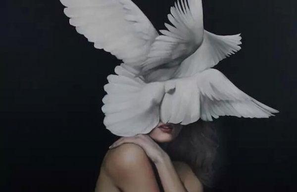 Kvinde med hvide duer foran hoved