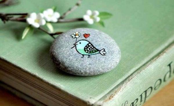 Fugl malet på sten bærer blomst