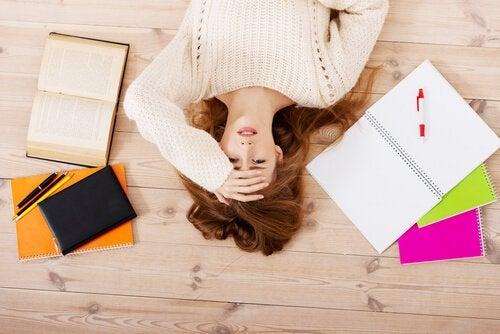 Kvinde ligger på gulv emd bøger omkring sig og venter på, at det er tid til at hvile