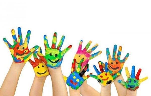 Børns hænder med farvede ansigter på