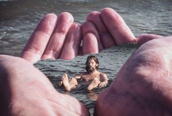 Mand i hav løftes op af kæmpe hænder