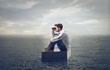 Mand med kikkert på hav