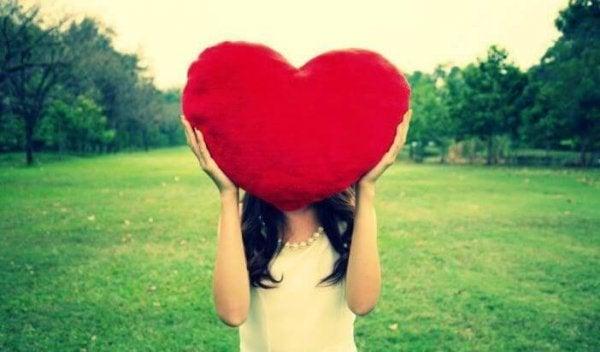 Pige med hjertepude foran ansigt
