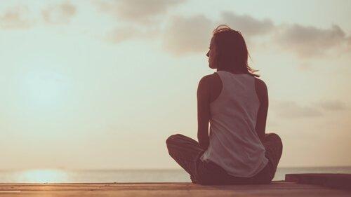 Kvinde ser mod horisonten og drømmer om at nå toppen