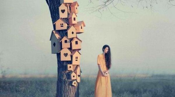 Kvinde ved siden af træ med huse på vælger at respektere naturen