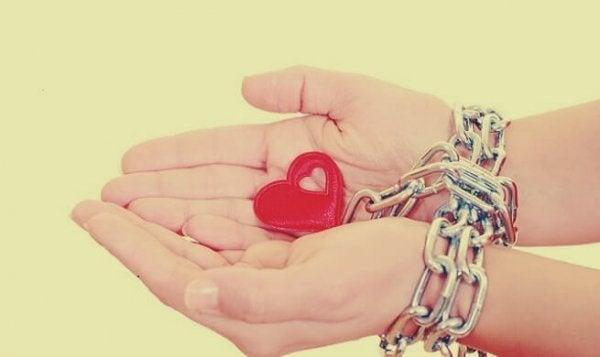 Hjerte er låst fast i hænder med kæder som symbol på falsk kærlighed