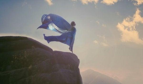 Kvinde på toppen af klippe bekæmper modgang