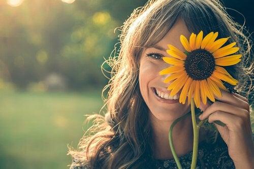 Smilende kvinde med solsikke er proaktiv