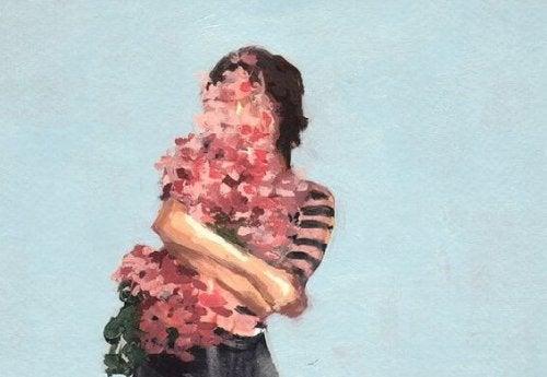 """Kvinde dækket af blomster ønsker sige """"jeg vil elske mig selv"""""""