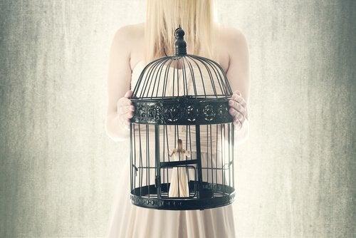 Kvinde står med lille person i bur af tillært hjælpeløshed