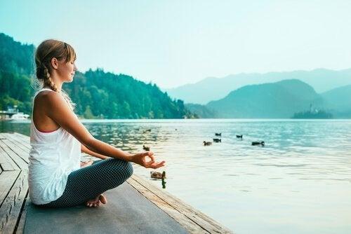 Kvinde dyrker yoga ved sø