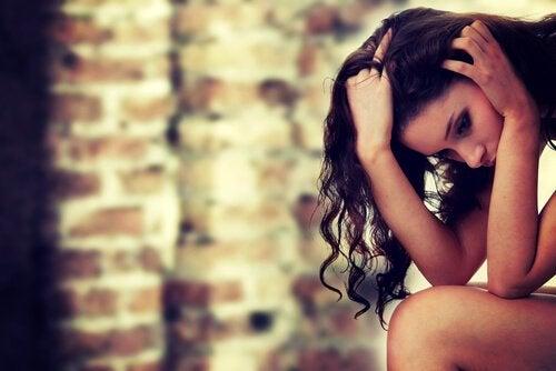 Kvinde foran mur føler skyldfølelse