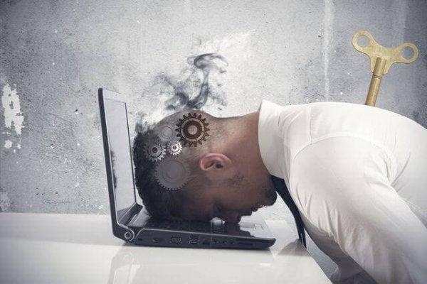 Mand med hovedet ned i PC oplever udbrændthedssyndrom, da han er afhængig af at arbejde