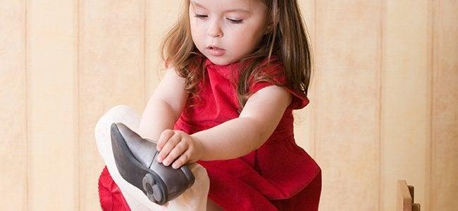 Pige øver sig i at tage sko på