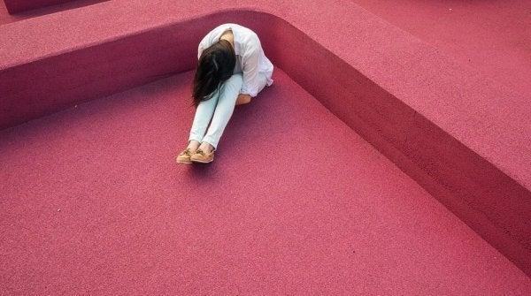 Kvinde på rødt gulv lider på grund af kronisk smerte