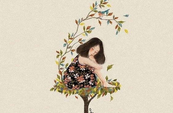 Pige sidder i træ af farverige blade