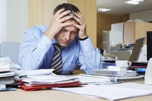 Mand på kontor tager sig til hoved som resultat af psykisk udmattelse