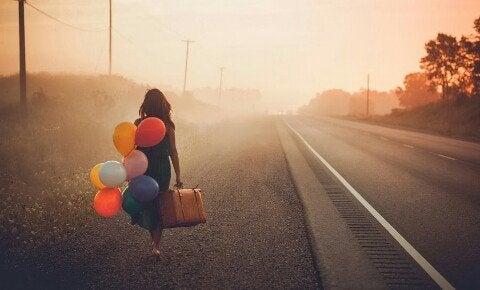 Kvinde går på vej med balloner