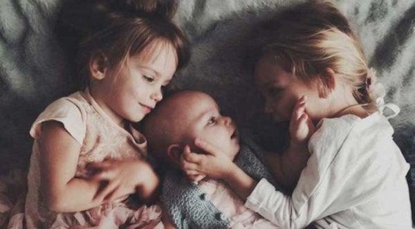 Ældre søskende krammer baby