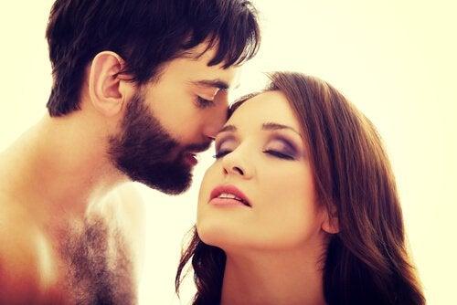 Mand kysser kvindes øre