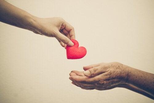 Person giver anden person hjerte som symbol på medlidenhed
