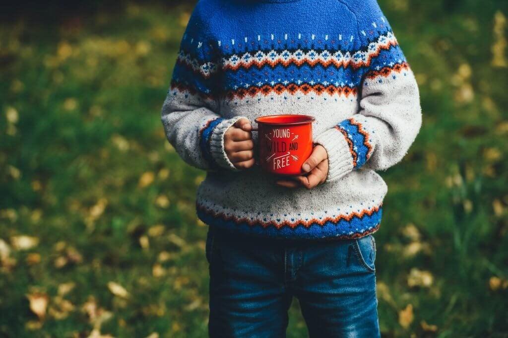 Barn med rød kop i hænderne