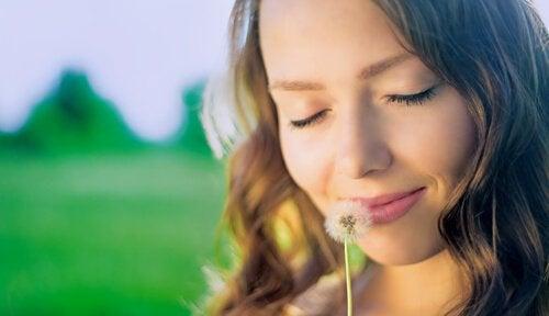 Kvinde smiler og dufter til blomst