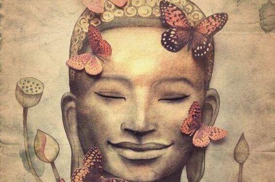 Statue af Buddha med sommerfugle belærer om buddhistisk psykologi