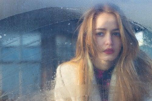 Kvinde ser ud af vindue med regn på