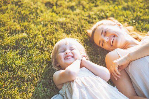 Mor og datter griner på græs, da hun ikke er en dårlig mor