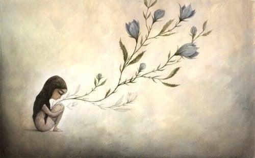 Grene med blomster vokser ud af kvinde