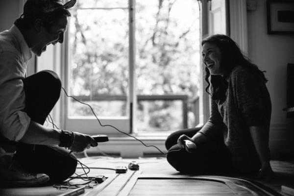 Par på gulv griner sammen