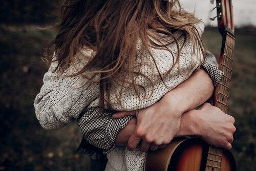 Mand med guitar krammer kvinde