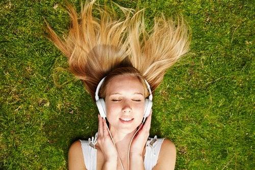 Kvinde på græs nyder effekten af musik