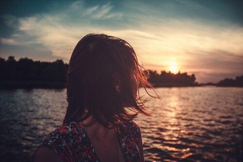 kvinder kigger bagud på soldnedgang i en flod. farvel.