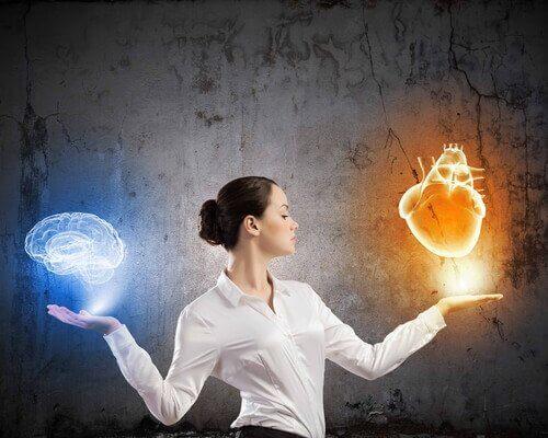 Kvinde står med hjerne og hjerte i hænder