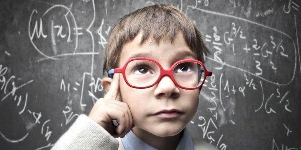 Barn med briller foran tavle