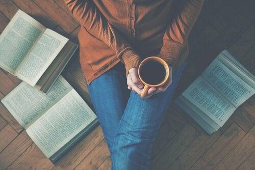 Kvinde på gulv sidder med kaffekop omringet af bøger