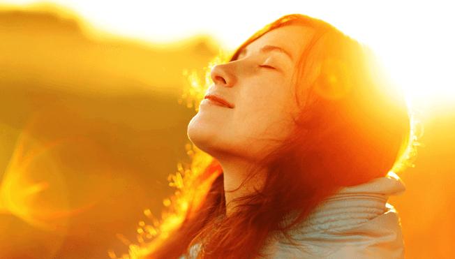 Kvinde ser op mod sollys