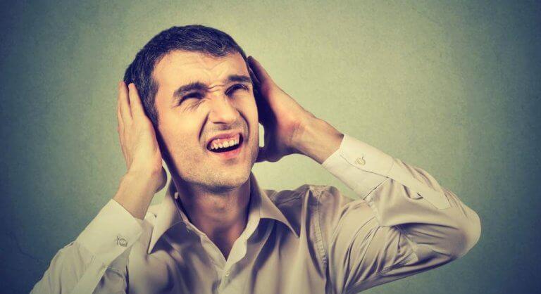 Mand med hænder for ørerne er generet af larm fra naboer