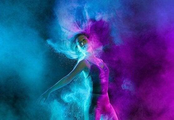 Kvinde danser i lilla og blå røg